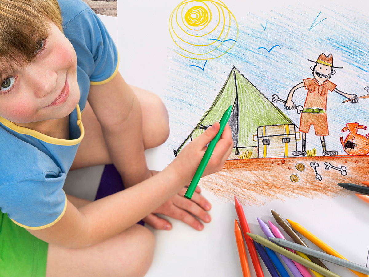 little boy drawing a boat with pencils