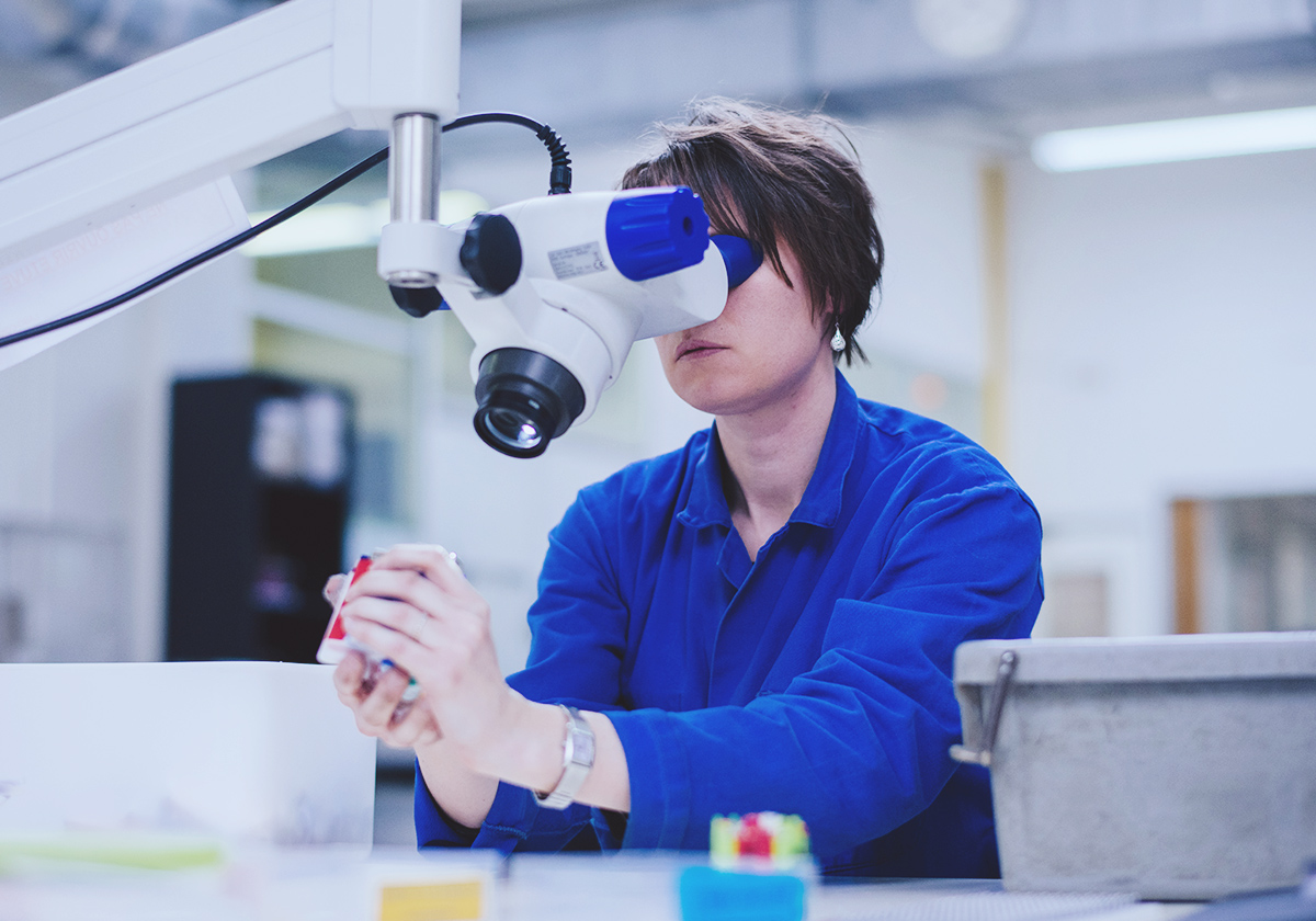 woman in blue overalls looking into a microscope