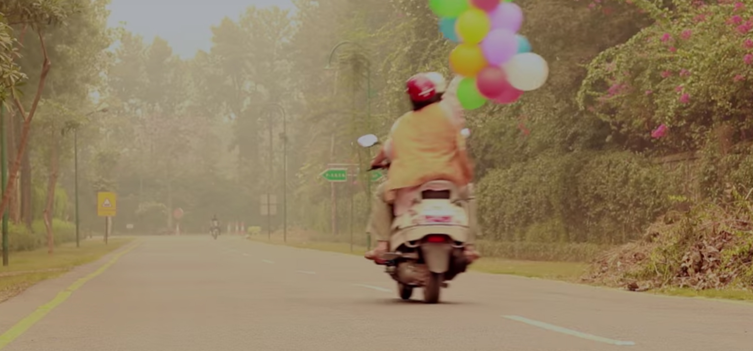 man on a motorcycle with a bouquet of balloons