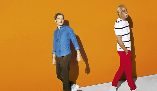 two men standing on an orange background