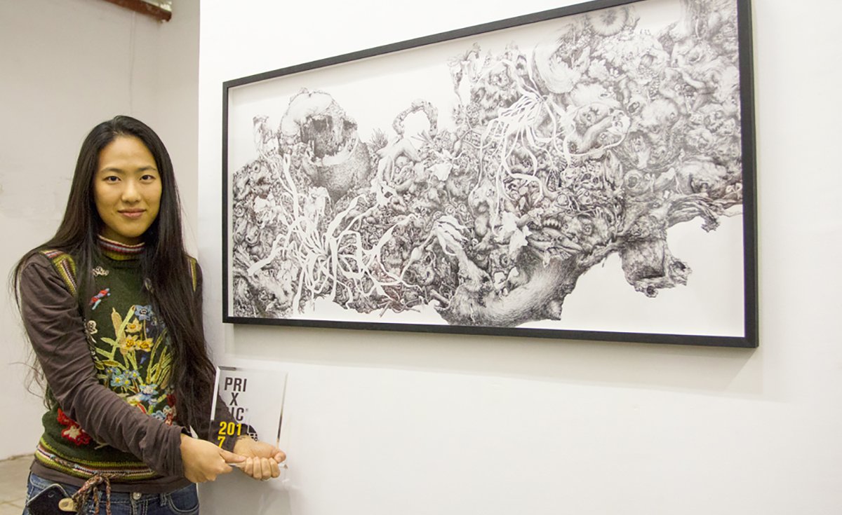 student holding a bic award in front of her work of art