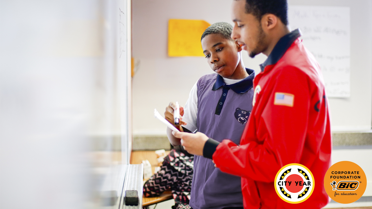 Student and mentor working at a dry erase board, with City Year and BIC Corporate Foundation logos