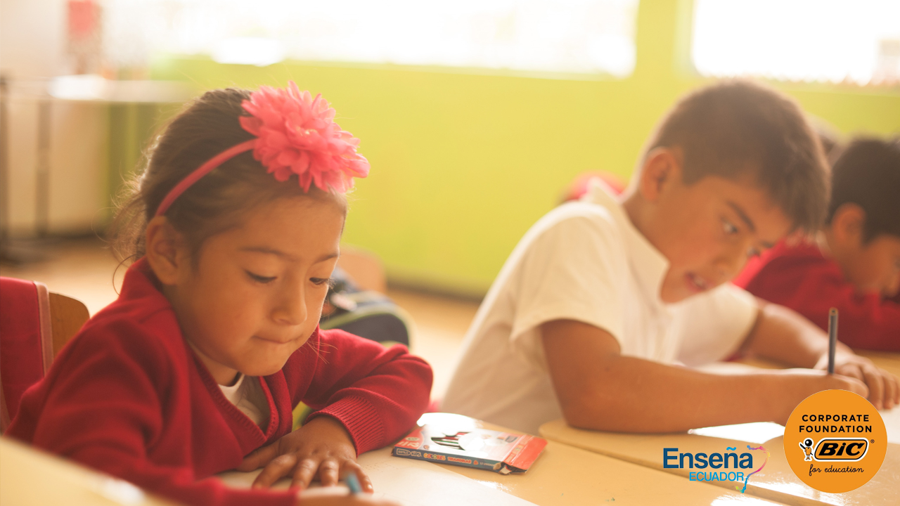 Boy and girl writing at their school desks, with Ensena Ecuador and BIC Corporate Foundation logos