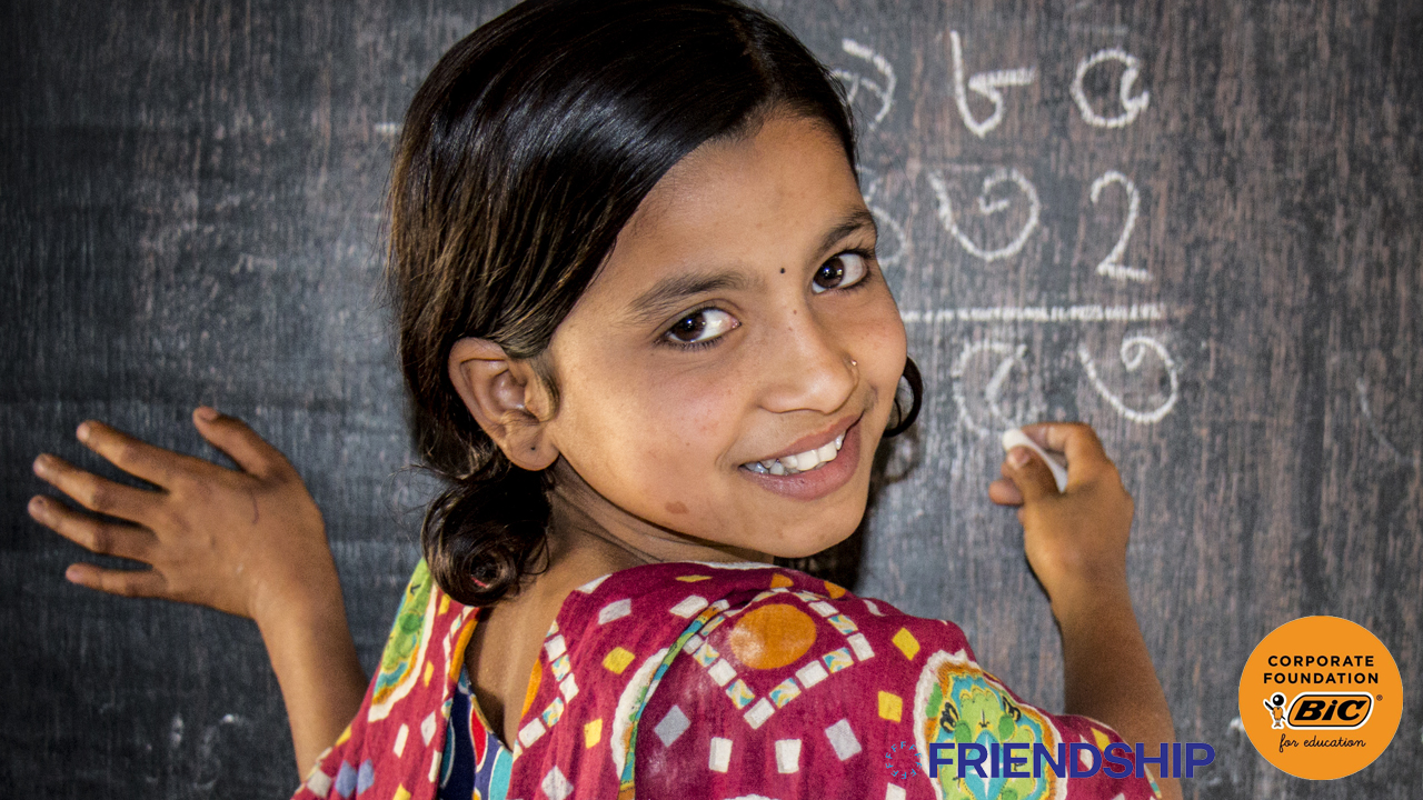 Girl looking behind her and smiling while writing on a chalkboard, with Friendship and BIC Corporate Foundation logos